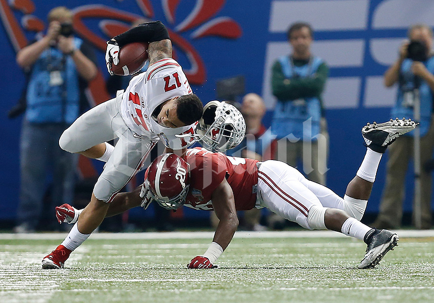 Ohio State Buckeyes running back Jalin Marshall (17) loses his helmet on a hard tackle from Alabama Crimson Tide defensive back Jarrick Williams (20) in the first quarter of the Allstate Sugar Bowl and College Football Playoff Semifinal at Mercedes-Benz Superdome in New Orleans, Thursday night, January 1, 2015. (The Columbus Dispatch / Eamon Queeney)