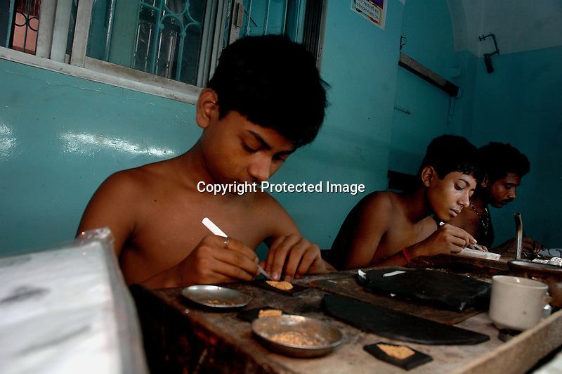 An Indian young boy along with his co workers working minutely with golden balls to make an expensive ornament. Kolkata, India  6/13/2007  Arindam Mukherjee
