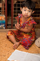 Myanmar, Burma. Bagan.  Little Burmese Girl, Pencils, and Writing Notebook.  She has thanaka paste on her face, a cosmetic sunscreen.
