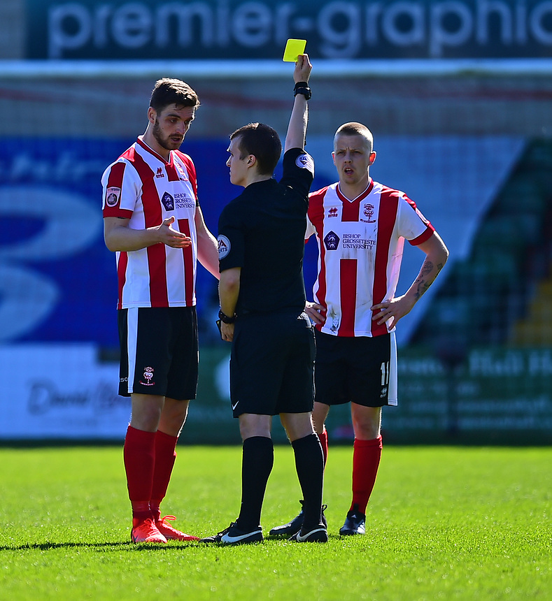 Lincoln City's Luke Waterfall is shown a yellow card by referee Antony Coggins<br /> <br /> Photographer Andrew Vaughan/CameraSport<br /> <br /> Vanarama National League - Lincoln City v Forest Green Rovers - Saturday 25th March 2017 - Sincil Bank - Lincoln<br /> <br /> World Copyright &copy; 2017 CameraSport. All rights reserved. 43 Linden Ave. Countesthorpe. Leicester. England. LE8 5PG - Tel: +44 (0) 116 277 4147 - admin@camerasport.com - www.camerasport.com