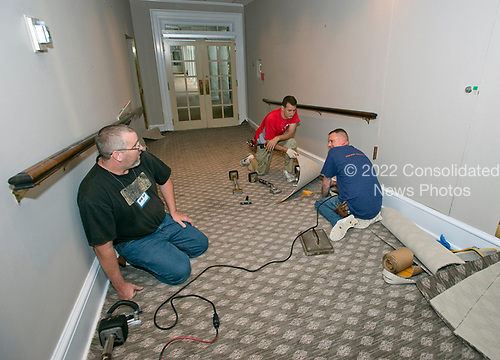 Carpet layers work in the White House West Wing in Washington, DC in the hallway that leads from the Upper Press Office to the Lower Press Office on onto the Colonnade as it is undergoing renovations while United States President Donald J. Trump is vacationing in Bedminster, New Jersey on Friday, August 11, 2017.<br /> Credit: Ron Sachs / CNP