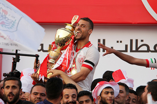 Palestinian players of Shabab Khan Younis football club celebrate with the trophy after beating Shabab Rafah during the final football match of the Palestine Cup for the southern governorates at Palestine stadium in Gaza city on April 30, 2018. Photo by Mahmoud Ajour