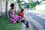 KINSHASA,DRC - NOVEMBER2: Esther Yandakwa, a 13-year old homeless child sits with a friend in a residential area (where many diplomats wealthy foreigners and congolese live) on the streets of Kinshasa DRC. She has lived on the streets since she was 6-7 years old and is dependent on prostitution to survive. She is walking the streets of Kinshasa to look for customers. She uses drugs and lives with a group of other homeless people in central Kinshasa. Thousands of children live on the streets of Kinshasa. Esther has been in and out orphanages or but she is only happy living in the mean streets of Kinshasa. (Photo by: Per-Anders Pettersson)