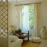 A tranquil sitting room separated by a trellised screen has a sofa and armchair upholstered in white linen