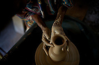 """A christian woman models pottery in a training center in Walleke, once an Ethiopian Jewish town in the outskirts of the city of  Gonder, northern Ethiopia on Saturday January 10 2009..Ethiopian Jews, who in the past were not allowed to own land, most of which was in the hands of the Orthodox church become able craftsmen producing pottery and threading cotton. All of them were airlifted to Israel through the years and none of them remains today in Walleke. Today the town is a tourist destination for whom are interested in The Beta Israelis and their history...Gonder hosts a population of around 9000 so called """"Falash Mura"""", supposed Ethiopian Jews who were forced to convert to Christianity. The Israeli Government is still verifying their claims  and if a clear link between them and Israel would be established they would have the right to return to their mother land. In the mean time Israeli and other Jewish non governmental organizations are working in support of this community."""