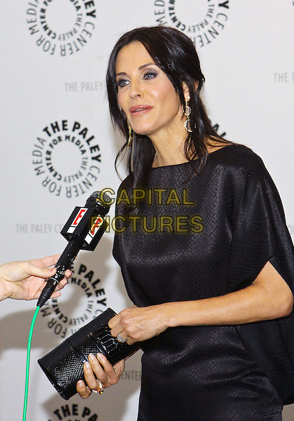 "COURTENEY COX ARQUETTE .27th Annual PaleyFest Presents ""Cougar Town""  held at the Saban Theatre, Beverly Hills California, USA..March 5th, 2010.half length black dress courtney  clutch bag  microphone interview funny silk satin .CAP/ADM/TC.©T. Conrad/AdMedia/Capital Pictures."