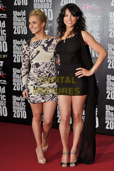 HAYDEN PANETTIERE & MICHELLE RODRIGUEZ.World Music Awards 2010 at the Sporting Club Monte Carlo, Monaco.May 18th, 2010 .full length black cream purple print dress mini beige patent heels nude shoes gold clutch bag long sleeve sleeved platform peep toe long train hand on hip sandals one shoulder .CAP/PL.©Phil Loftus/Capital Pictures.