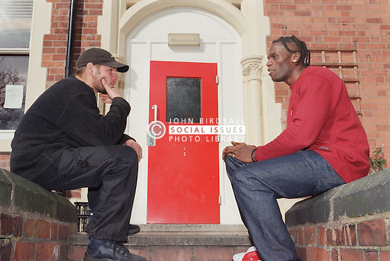 Support worker and resident sitting outside Young Persons' Resettlement hostel talking,