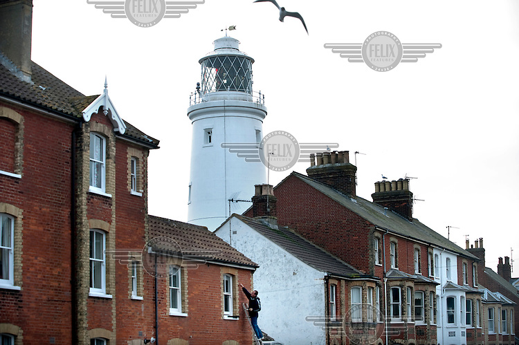 A seagull flies over a street in Southwold, Suffolk with its 19th Century Lighthouse in the background....