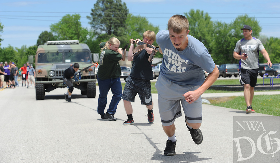 NWA Democrat-Gazette/ANDY SHUPE<br /> Quinn McClain, 15, a freshman at Elkins High School, leads a team of fellow freshman students Tuesday, May 2, 2017, to pull a Elkins Police HMMWV, a former military vehicle weighing nearly 6,000 pounds, in a competition between classes in the annual Herd Wars at the school. Students pay a dollar to attend the games, which include court games and obstacle courses, to fund a scholarship for an Elkins student.