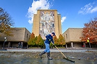 """November 5, 2019; Joe Negri from the Notre Dame maintenance department squeegees out the muck at the bottom of the just-drained Hesburgh Library reflecting pool. The annual job turns up mostly leaves and sediment with some odds and ends and even some coins. """"We have gotten up to $60 if you're willing to dig through the muck,"""" Joe said. (Photo by Matt Cashore/University of Notre Dame)"""