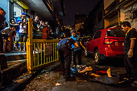 MANILA, PHILIPPINES - OCTOBER 06: Scene of the Crime Police investigators, SOCO, conduct their investigation of surrenderee, Ryan Santillian, 29, as he lays dead in the middle of the street in the neighborhood of Makati on October 6, 2016 in Manila City, Philippines. Bystanders heard 6 gunshots around 9pm and found Mr Santillian dead in the street. The unknown gunman was on foot and shot the victim with a silencer according to eyewitnesses. Mr Santillian had surrendered himself in early July and was on the list of users that was in rehabilitation. Ryan left a wife and 2 children.  <br /> Photo by Daniel Berehulak for The New York Times