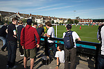 Home supporters watching the first-half action at the Mersey Travel Arena, home to Marine Football Club (in white), as they played host to Ilkeston FC in a Northern Premier League premier division match. The match was won by the home side by 3 goals to 1 and was watched by a crowd of 398. Marine are baed in Crosby, Merseyside and have played at Rossett Park (now the Mersey Travel Arena)  since 1903, the club having been formed in 1894.