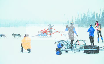A group of bikers out for a test ride for the next week's Extreme event wave to a passing musher during a snowstorm Saturday.