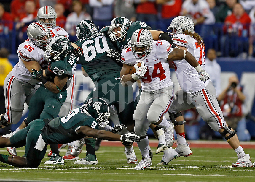 Ohio State Buckeyes running back Carlos Hyde (34) carries the ball up the middle and past Michigan State Spartans safety Isaiah Lewis (9) in the 3rd quarter during the Big 10 Championship game at Lucas Oil Stadium in Indianapolis, Ind on December 7, 2013.  (Dispatch photo by Kyle Robertson)
