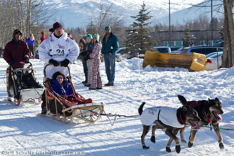 Aaron Burmeister and team run past spectators on the bike/ski trail during the Anchorage ceremonial start during the 2013 Iditarod race.    Photo by Britt Coon/IditarodPhotos.com