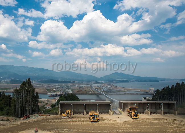 Photo shows the the view of rebuilding project from a hilltop in Rikuzentakata, Iwate Prefecture, Japan. Atlas Copco drill rigs are a key feature of the project, which will shift blasted rubble from a nearby hillside to the central part of the city, which was flattened by the 2011 tsunami, where the land will be raised 10 meters. Rubble is transferred to the lower lying coastal land via a 3-km-long conveyor belt system. Rob Gilhooly Photo
