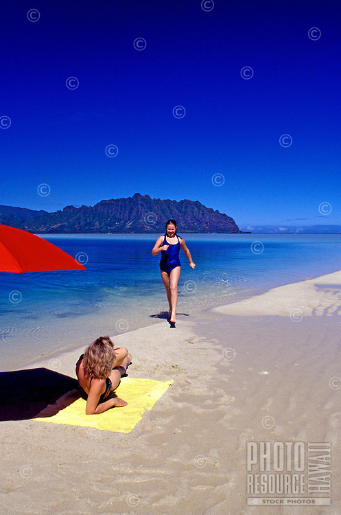 A woman runs at low tide on the white sandbar  known as 'Ahu O Laka', in Kaneohe Bay, while another woman sunbathes on a yellow towel shaded by a bright red umbrella.