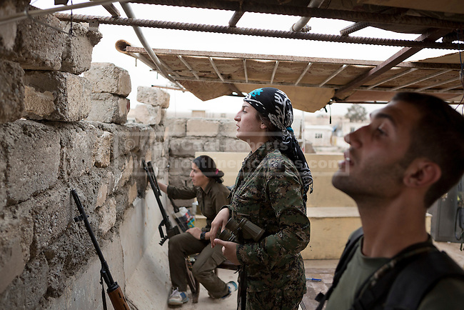 28/09/2014. Rabia, Iraq. Fighters belonging to the Syrian-Kurdish YPG and YPJ observe Islamic State territory from a YPG position in the Iraqi border town of Rabia.<br /> <br /> Facing each other across the Iraq-Syria border, the towns of Al-Yarubiyah, Syria, and Rabia, Iraq, were taken by Islamic State insurgents in August 2014. Since then The town of Al-Yarubiyah and parts of Rabia have been re-taken by fighters from the Syrian Kurdish YPG. At present the situation in the towns is static, but with large exchanges of sniper and heavy machine gun fire as well as mortars and rocket propelled grenades, recently occasional close quarter fighting has taken place as either side tests the defences of the other.