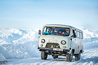 Skiers traveling in Kyrgyzstan drive on a  snowy road in a Russian made UAZ 452