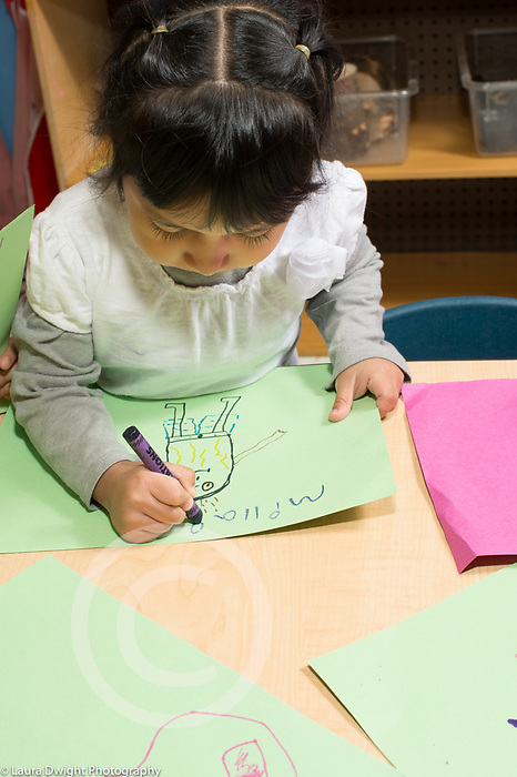 Education Preschool 4 year olds girl writing her name on artwork