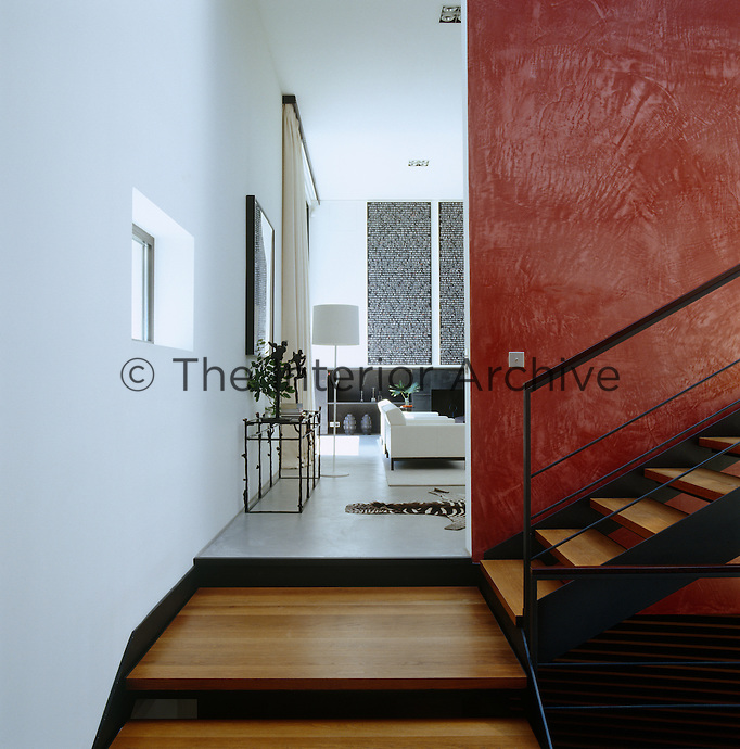 The modern metal and wood staircase leads to the spacious living room