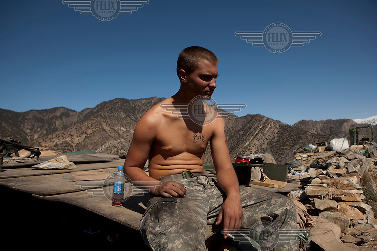 US Army Soldier Private First Class Hayden from Viper Company 126, 1st Platoon, rests at an Outpost near Restrepo Firebase in the restive Korengal Valley. Restrepo, a remote outpost, is known as one of the most violent places in Afghanistan. Located in the Korengal Valley it comes under fire on a daily basis from Anti-Afghan Forces in the local villages and mountains.