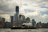 The space shuttle Enterprise is towed by barge up the Hudson River in New York with the World Trade Center's Freedom Tower in the background while on it's way to the Intrepid Sea, Air and Space Museum where it will be permanently displayed, Wednesday, June 6, 2012. .Mandatory Credit: Bill Ingalls / NASA via CNP