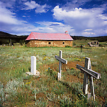 Adobe church with red corrugated roof, headstone, blue sky with light clouds, in a clearing of the forest. San Isidro, New Mexico.