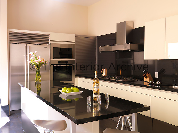 The modern white lacquered kitchen features black granite work surfaces and stainless steel appliances