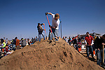 Volunteers man a mound of sand in the parking lot of the Fargodome in Fargo, N.D., on April 8, 2009, as part of the community's effort to build a stockpile of sandbags.