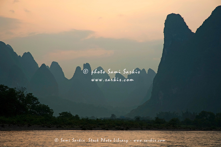 Looking across the Li Jiang River at the limestone mountain peaks between Xinping and Yangshuo, Guangxi, China.