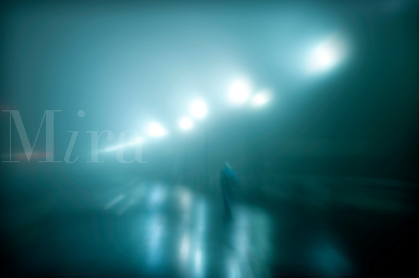 Figure walking on a wet foggy night.