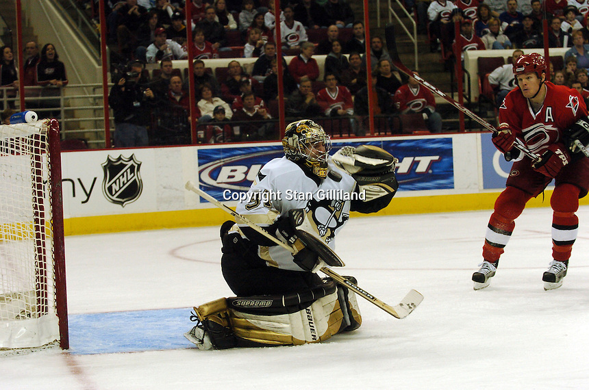 The Pittsburgh Penguins' goaltender Sebastien Caron takes a shot to the facemask as Carolina Hurricanes' Kevyn Adams looks on in Raleigh, NC Friday, February 10, 2006. The Penguins won the game 4-3.
