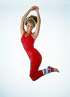 Christie Brinkley jumps in red leotard and striped leg warmers. Studio shoot, Los Angeles, 1982. Photo by John G. Zimmerman.