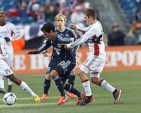 Sporting Kansas City midfielder Benny Feilhaber (10) dribbles as New England Revolution defender Kelyn Rowe (11) defends.  In a Major League Soccer (MLS) match, Sporting Kansas City (blue) tied the New England Revolution (white), 0-0, at Gillette Stadium on March 23, 2013.