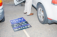 """Supporters of US President Donald Trump hold signs outside the Holy Name Parish Hall polling place as people arrive to vote in the Massachusetts presidential primary on Super Tuesday in West Roxbury, Massachusetts, on Tue., March 3, 2020. A sign reading """"Blue Lives Matter"""" is seen on the ground."""