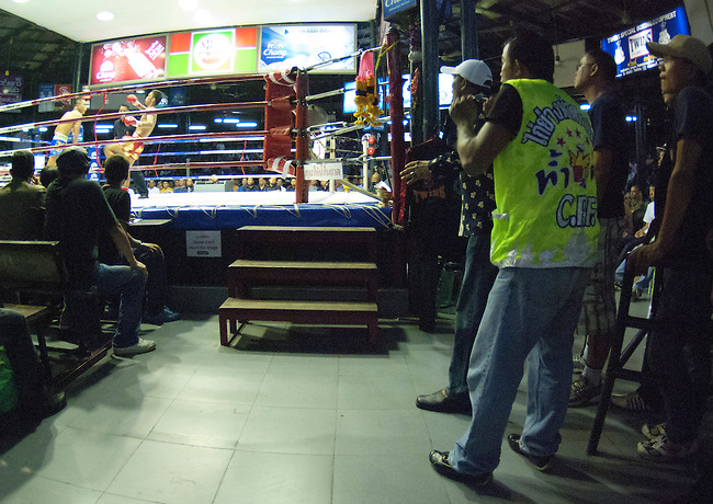 Bangkok, August 30, 2011, Lumpini Muay Thai kick boxing stadium; trainers from Kai Yang Ha Dao gym watch as their fighter Akemongkol battles Yodvicha