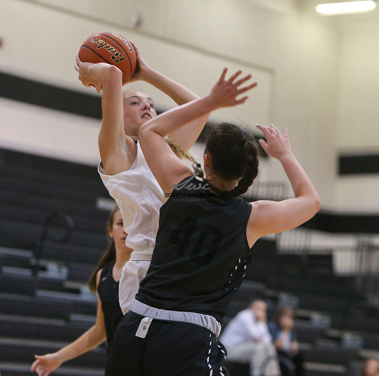Vandegrift Vipers guard Jen Moore (12) looks to shoot over Cedar Park Timberwolves post Nicole Leff (40) during a girls high school basketball game between the Vandegrift Vipers and the Cedar Park Timberwolves at Vandegrift High School in Austin, Texas on November 14, 2017.