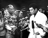 Legendary former Heavyweight Champion Joe Lewis looks on as current Heavyweight Champion Muhammad Ali speaks to reporters at the weigh-in ceremony prior to the fifteen round heavyweight title fight against challenger Alfredo Evangelista of Spain at the Capitol Centre in Landover, Maryland on May 15, 1977.  Ali tipped the scales at 221 1/2 pounds.  Ali's purse will be $2.7 million and Evangelista will receive $85,000.<br /> Credit: Arnie Sachs / CNP