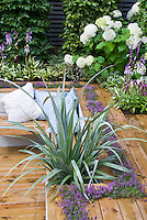 Sunken deck landscaping with raised beds, hydrangea shrubs, astelia spearlike specimen plant, flowers, spiky plants, garden bench with pillows, Hostas in bloom, thymes herbs in crevices, pillows, wall, for overal pretty and colorful outdoor room