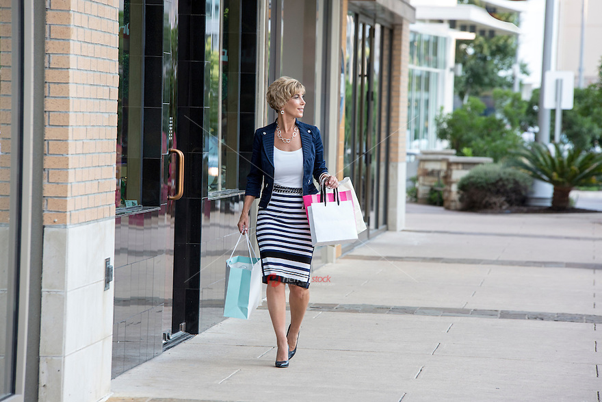 Elegant female mall shopper with shopping bags is in retail heaven at a popular Austin outdoor shopping center