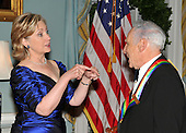 Washington, DC - December 5, 2009 -- United States Secretary of State Hillary Rodham Clinton and 2009 Kennedy Center honoree Mel Brooks engage in an animated conversation as they prepare pose for the formal group photo with the other honorees following the Artist's Dinner at the United States Department of State in Washington, D.C. on Saturday, December 5, 2009. .Credit: Ron Sachs - Pool via CNP