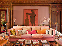 A grand sitting room, decorated in pastel colours, predominantly pink, with gilded mouldings and parquet flooring. A contemporary sofa designed by Henri Quinta dominates the room.