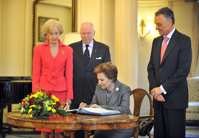 AUSTRALIA, Canberra : Australian Governor General Quentin Bryce, Michael Bryce and President Anibal Cavaco Silva watch as Maria Cavaco Silva signs the visitors book at Government House, Canberra Australia on May 25, 2012. AFP PHOTO/Mark GRAHAM