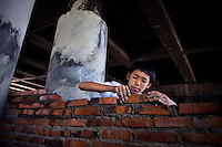 A student at Kartini Emergency School builds a wall with bricks and cement after years of using only scrap wood and sheet metal. The teachers and students are directly involved in everything that has to do with the school including daily maintenance, sustenance and logistical operations. Acquiring practical skills, like brick-laying, is an important part of the education programme. Since the early 1990s, twin sisters Sri Rosyati (known as Rossy) and Sri Irianingsih (known as Rian) have used their family inheritance to set up and run 64 schools in different parts of Indonesia, providing primary education combined with practical skills to some of the country's most deprived children..