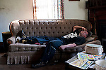 Cameron Blosser lies on the couch in his living room after hurting his back helping his father move firewood.