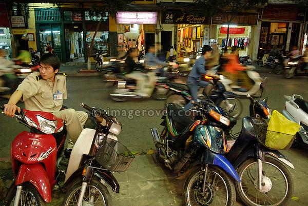 Asia, Vietnam, Hanoi. Hanoi old quarter. Boared watchman guarding the parked motorbikes.