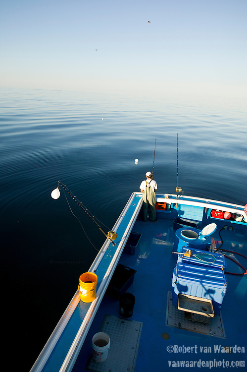 A fisherman waits for a bite while blue fin tuna fishing on the Gulf of St. Lawrence near North Rustico, Prince Edward Island, Canada.