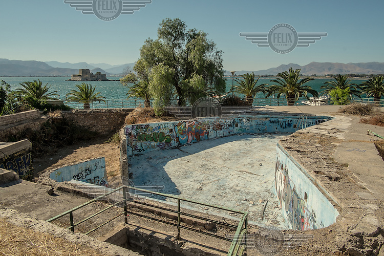 NAFPLIO, GREECE: an abandoned swimming pool by the sea shore.